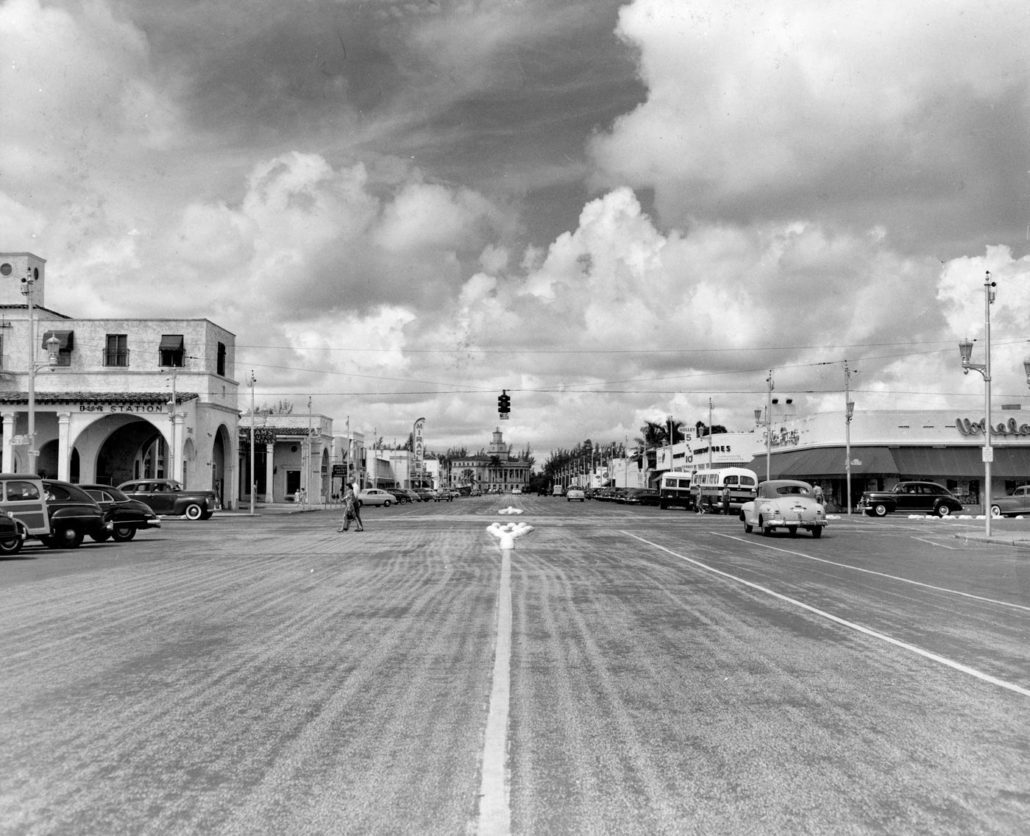 Street view of Miracle Mile from Ponce de Leon Blvd looking west in the 1950 shows a 1920s Mediterranean style buildings mixed with 1940s modern style buildings, as well as raised pavement markers that predated the median landscape project. Image courtesy of HistoryMiami Museum, 1995-410-106.