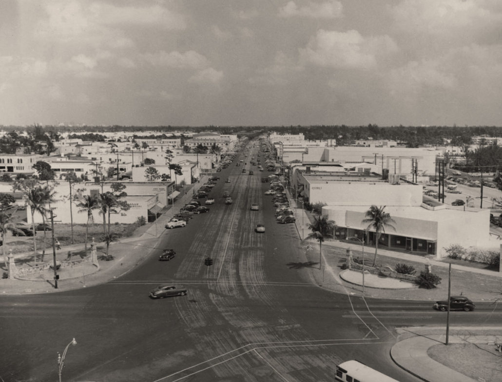 Street view of Miracle Mile from City Hall looking east in the 1940s shows an emerging development with one-to-two story modern-style commercial buildings, bus transportation, parking lots, and trees that are the remnants of the natural landscape. Image courtesy of Coral Gables Historical Resources